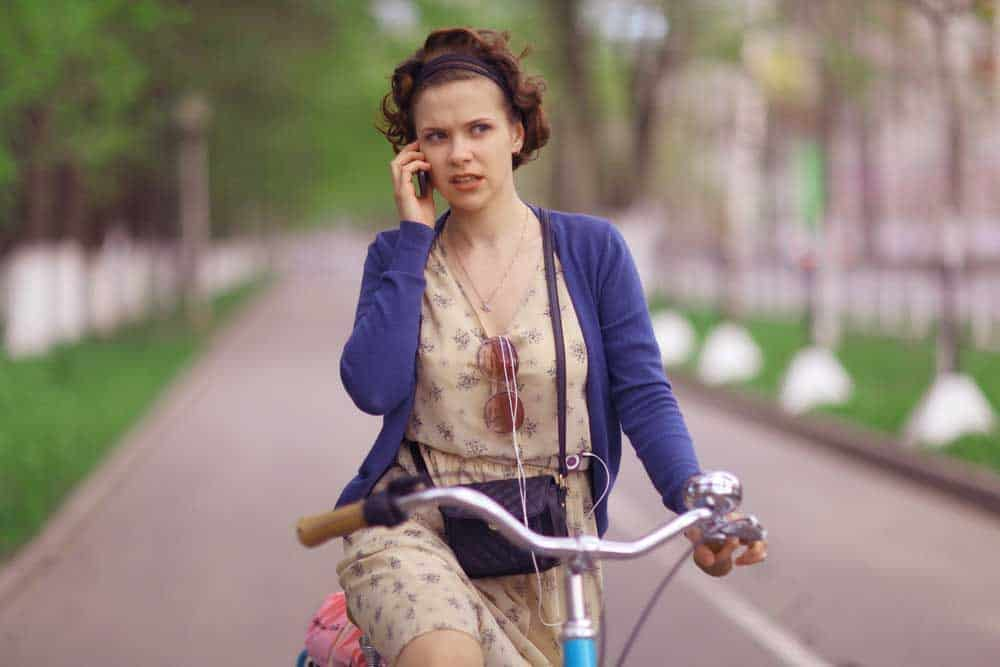 Woman riding her bike while on the phone